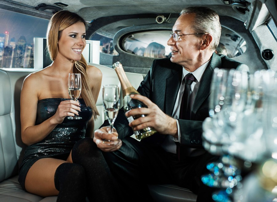 sugardaddy in a limousine with young woman